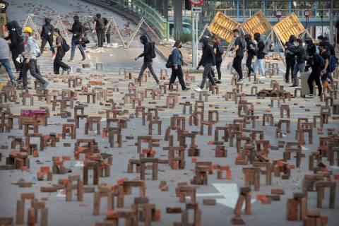 Protesters walk past barricades of bricks on a road near the Hong Kong Polytechnic University i ...