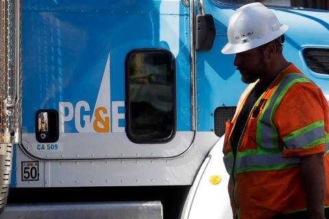 In an Aug. 15, 2019, file photo, a Pacific Gas & Electric worker walks in front of a truck in S ...
