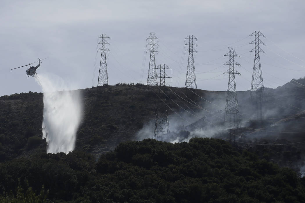 FILE - In this Oct. 10, 2019, file photo, a helicopter drops water near power lines and electri ...