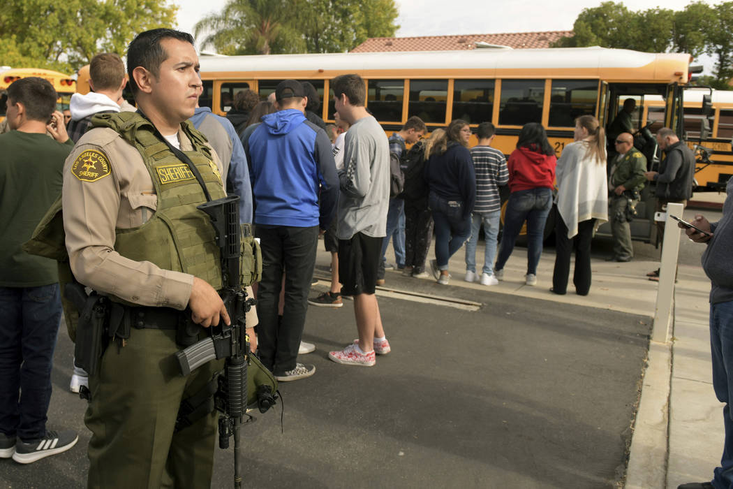 Students evacuate their campus after a gunman opened fire at Saugus High School on Thursday, No ...