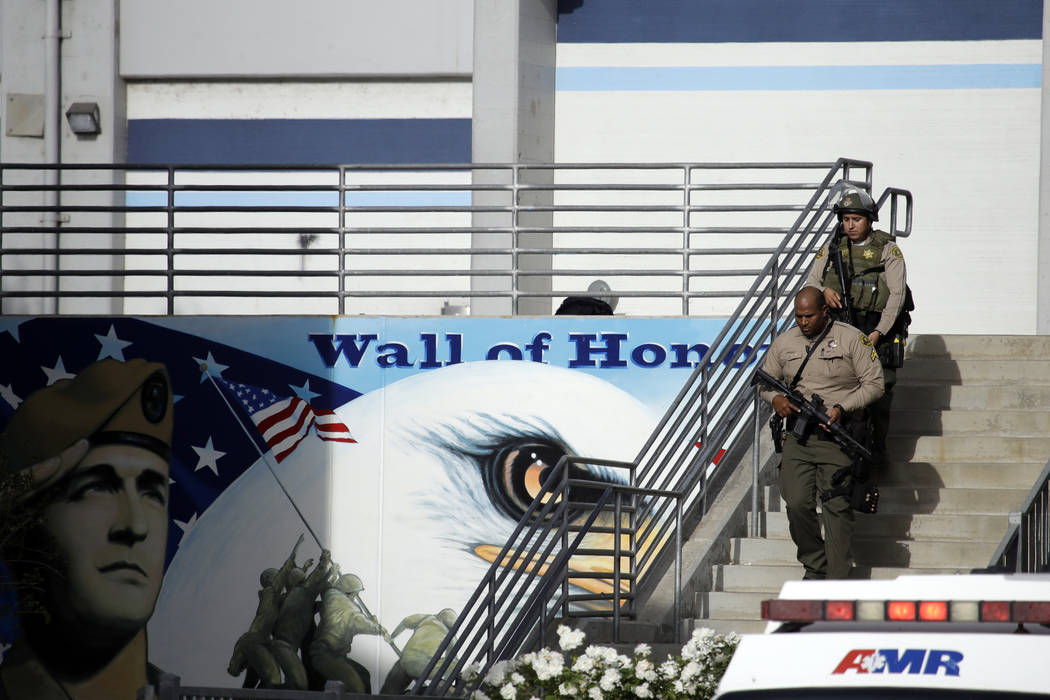 Law enforcement personnel walk with their weapons drawn outside of Saugus High School after rep ...