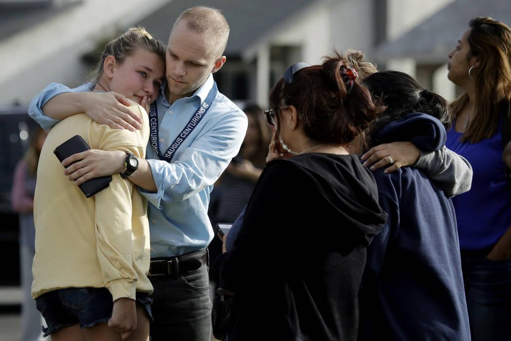 D.J. Hamburger, center in blue, a teacher at Saugus High School, comforts a student after repor ...