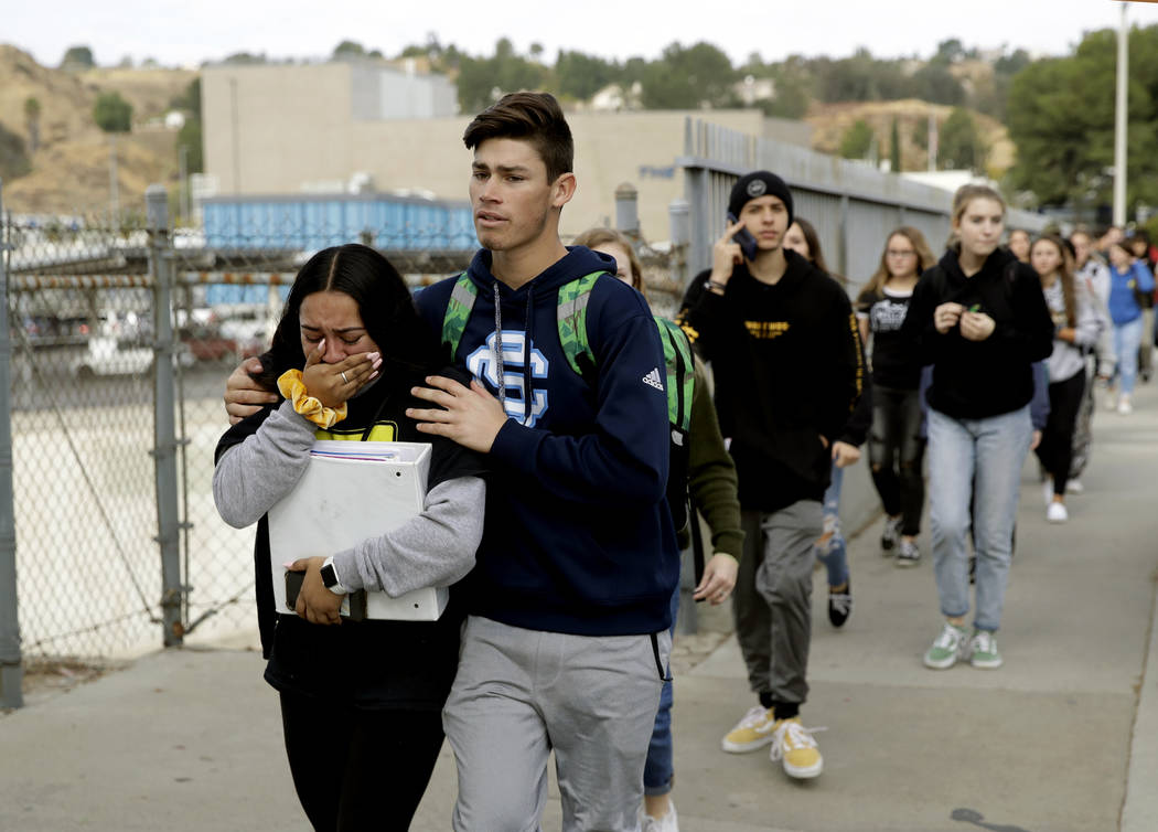 Students are escorted out of Saugus High School after reports of a shooting on Thursday, Nov. 1 ...