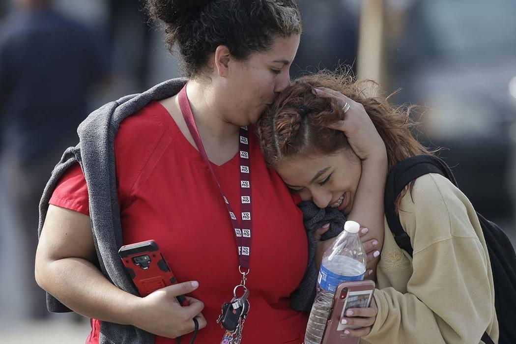 Parent Alicia Leon, left, kisses her daughter, Alejandra Cruz, a tenth grader, as they reunite ...