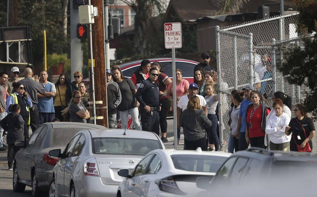 Parents wait to be reunited with students at the Esteban Torres High School in unincorporated E ...