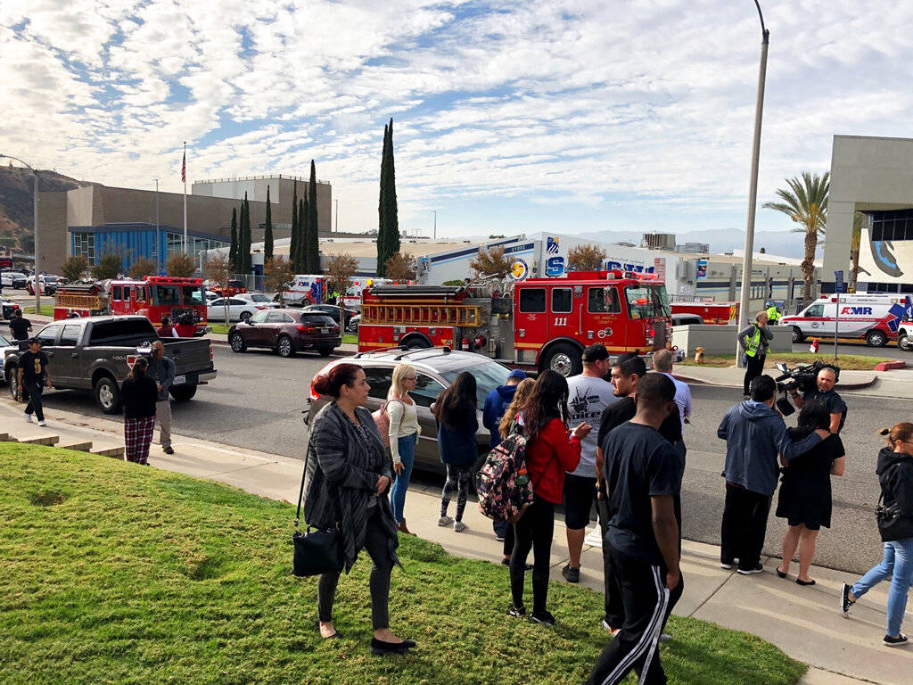 People wait for students and updates outside of Saugus High School after reports of a shooting ...