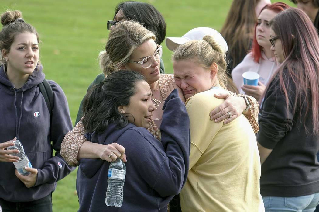 Students are comforted as they wait to be reunited with their parents following a shooting at S ...