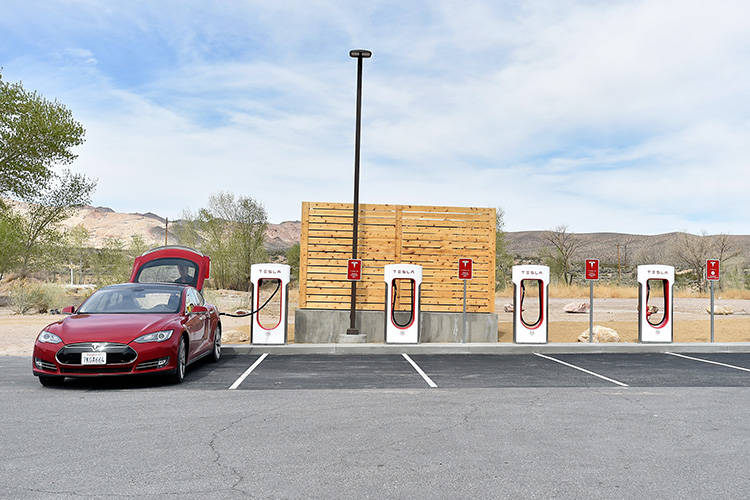 A Tesla electric car is seen charging before the dedication first electric car charging station ...