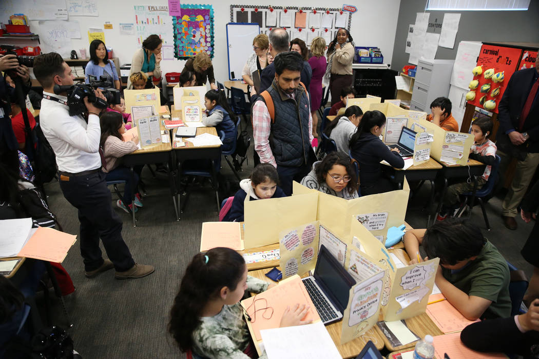 Educators including Sal Khan, center, founder of Khan Academy, tour of a classroom at Crestwood ...
