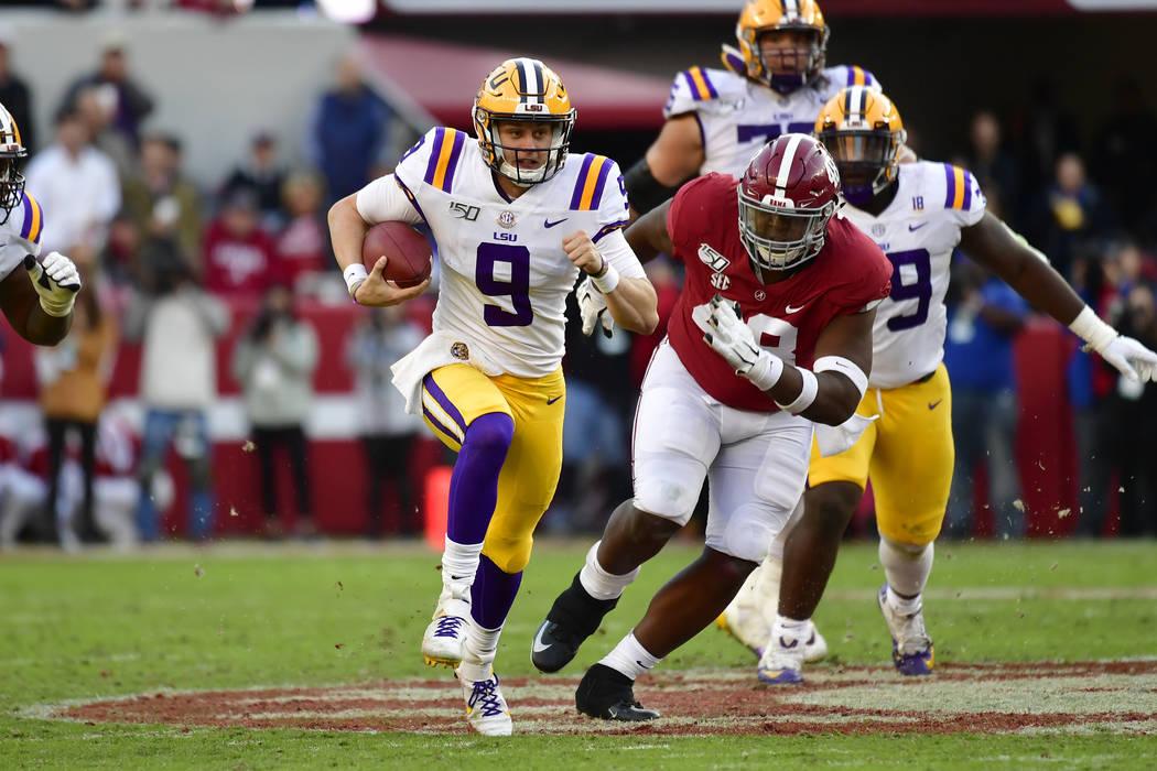 LSU quarterback Joe Burrow (9) runs as Alabama defensive lineman Phidarian Mathis (48) chases h ...