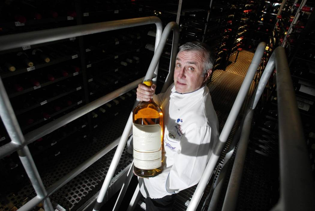 Longtime Las Vegas restaurateur Andre Rochat displays a bottle from inside the wine cellar of h ...