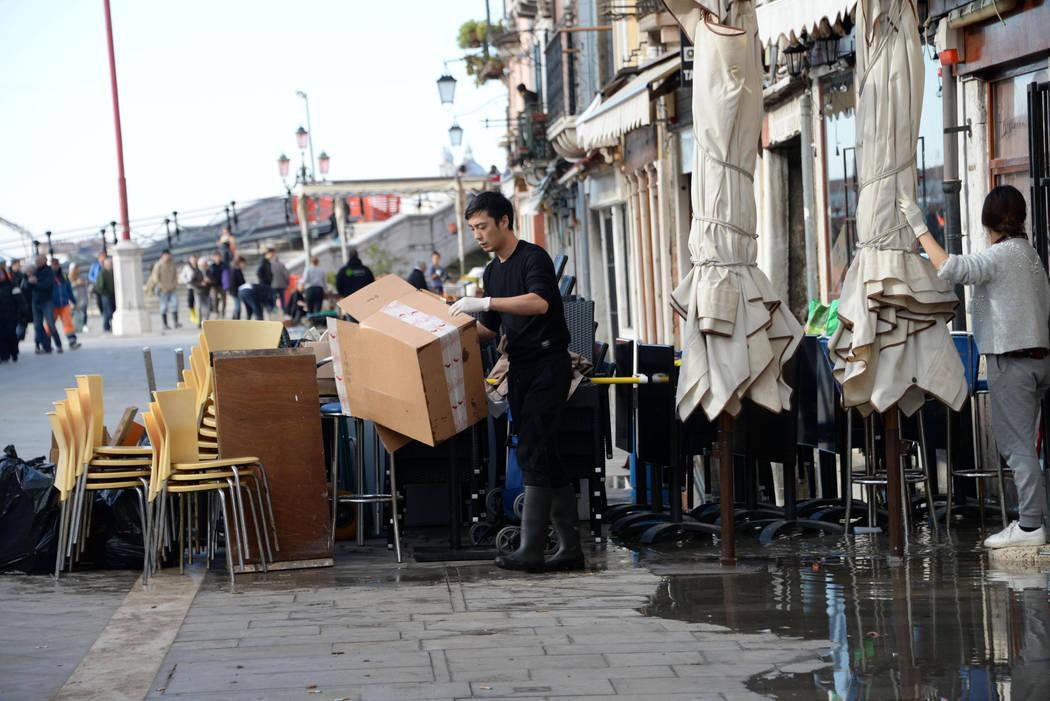 A man cleans up following a flooding in Venice, Italy, Thursday, Nov. 14, 2019. The worst flood ...