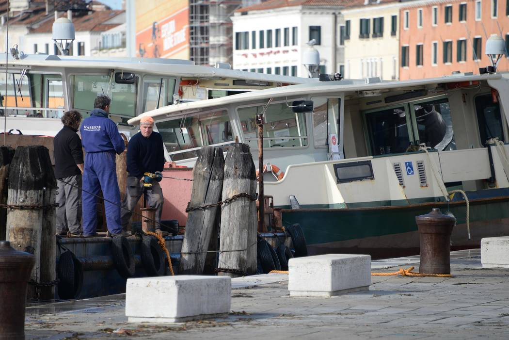 People work to fix damages following a flooding in Venice, Italy, Thursday, Nov. 14, 2019. The ...