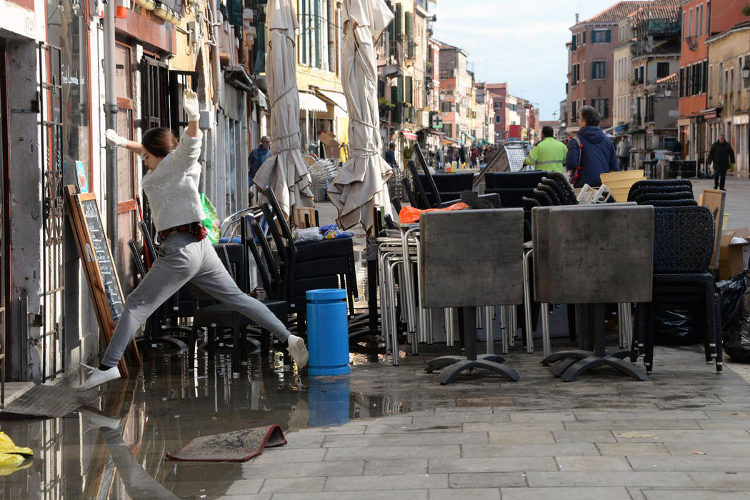 A woman jumps over a puddle during cleaning following a flooding in Venice, Italy, Thursday, No ...