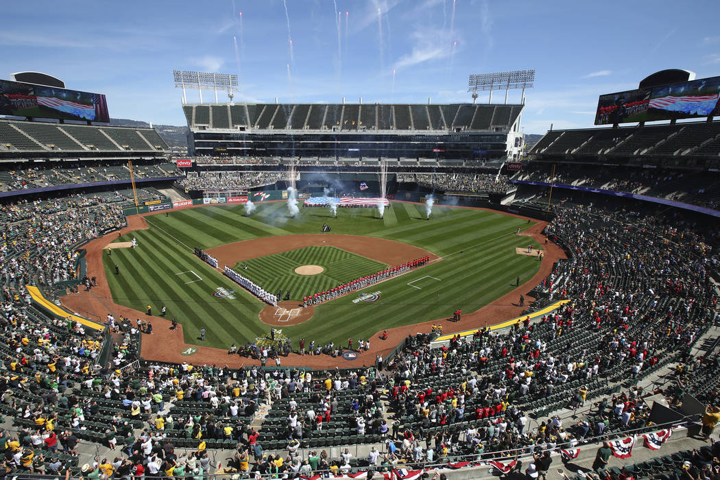 The Los Angeles Angels and the Oakland Athletics stand for the national anthem at Oakland Colis ...