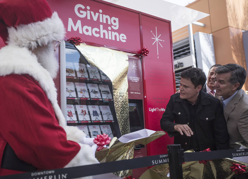 Donny Osmond and Santa Claus unveil the Giving Machine, a vending machine that offers different ...