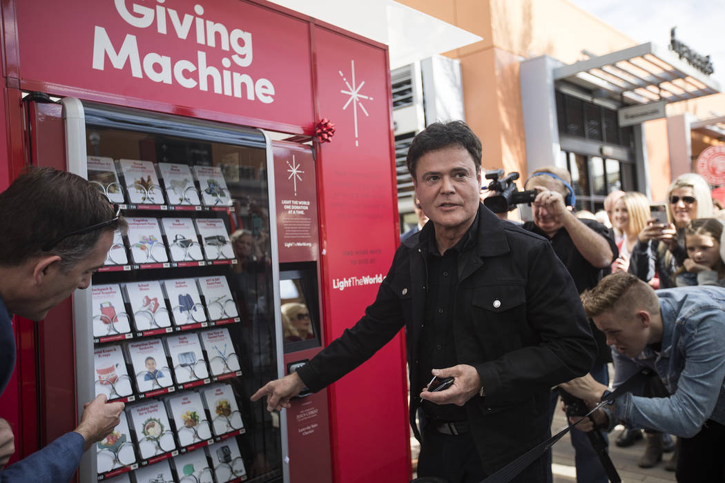 Donny Osmond purchases from the Giving Machine, a vending machine that offers different items f ...