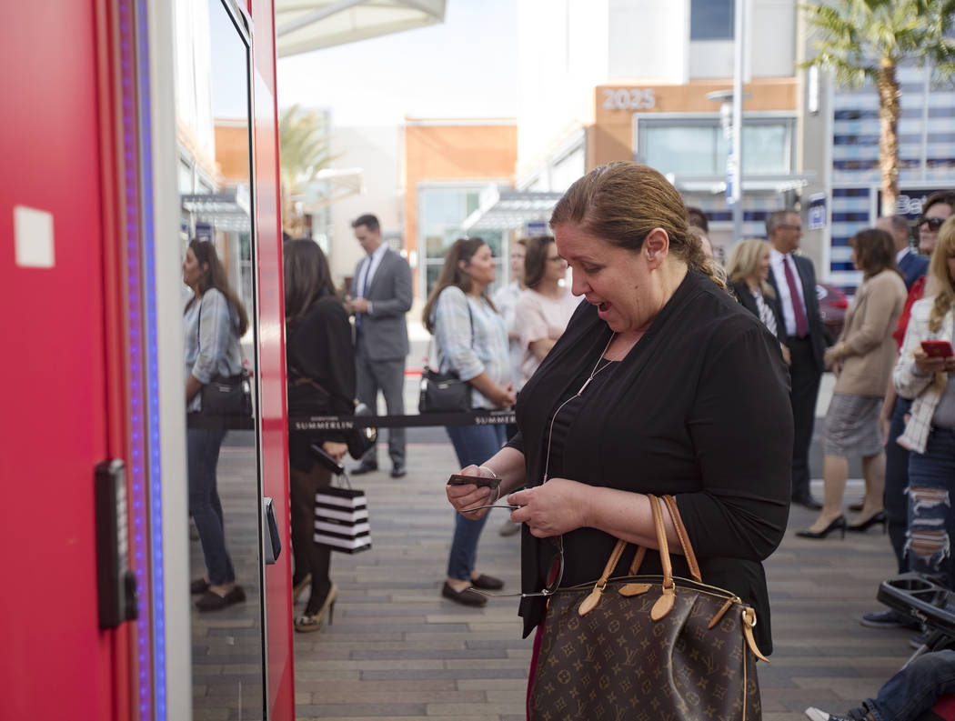 Susan Summers uses the Giving Machine, a vending machine that offers different items from chari ...