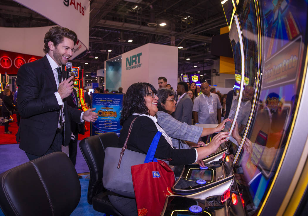 Jessica Savare, center, enjoys a turn at the Cleopatra game on display in the IGT exhibition sp ...