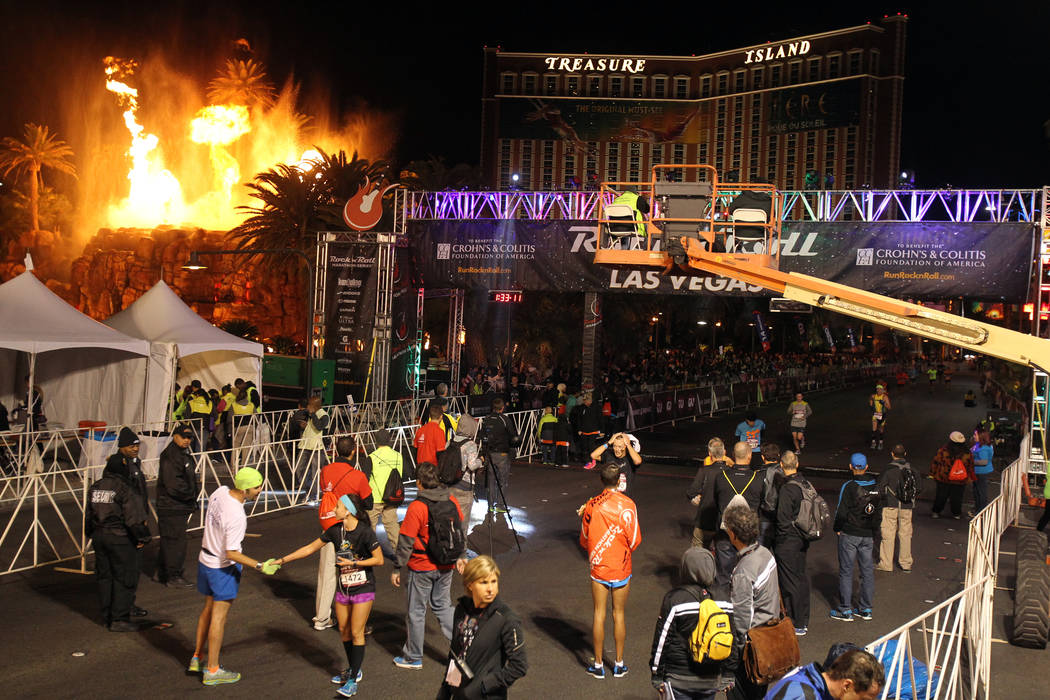The Mirage volcano goes off as runners cross the half marathon finish line in the Las Vegas Roc ...
