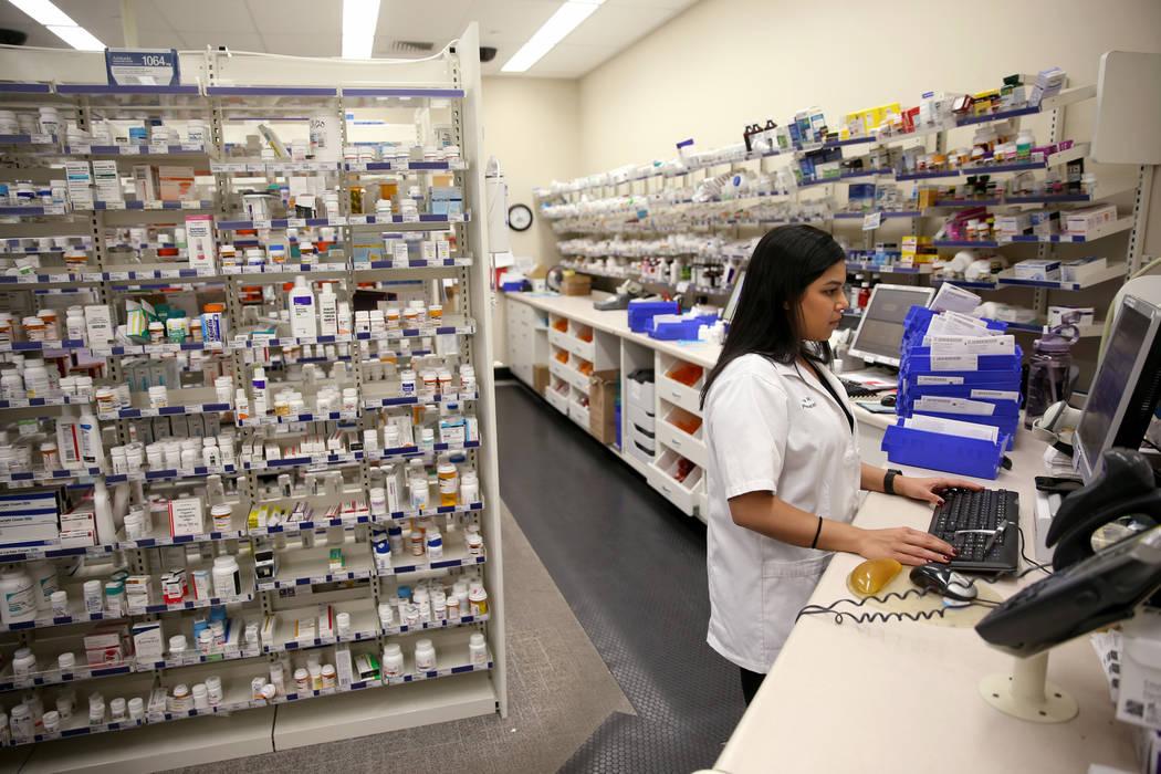 Pharmacy Manager Maria Masood fills a customer's prescription at the Walgreens pharmacy on Blue ...