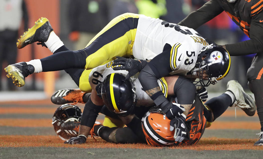 Cleveland Browns defensive end Myles Garrett, bottom, and, Pittsburgh Steelers center Maurkice ...
