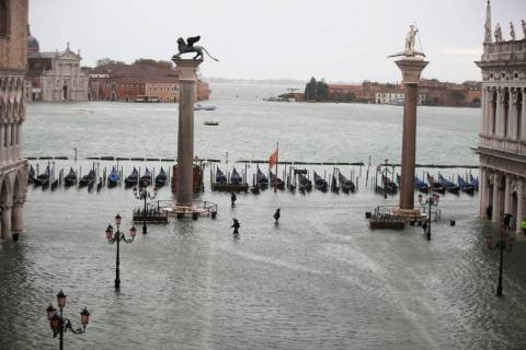 People make their way in a flooded St. Mark's Square in Venice, Italy, Friday, Nov. 15, 2019. ...