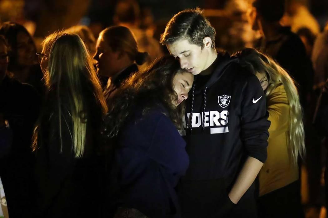 Hannah Schooping-Gutierrez, center, a student at Saugus High School, is comforted by her boyfri ...