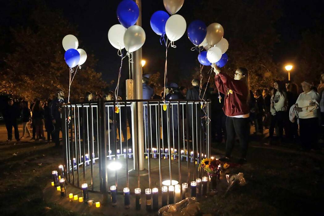 Jessica Dumont, a former student at Saugus High School, places balloons on a makeshift memorial ...