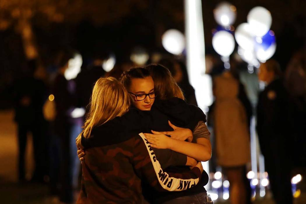 Students embrace during a vigil at Central Park in the aftermath of a shooting at Saugus High S ...