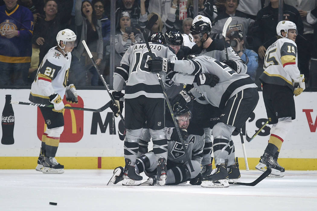 The Los Angeles Kings celebrate the go-ahead goal by Jeff Carter, bottom, during the third peri ...