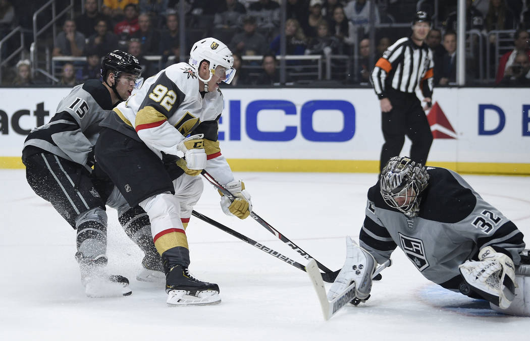 Los Angeles Kings goalie Jonathan Quick, right, makes a save on a shot by Vegas Golden Knights ...