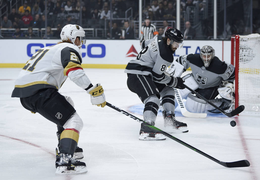 Los Angeles Kings defenseman Drew Doughty, center, chases down the puck past Vegas Golden Knigh ...