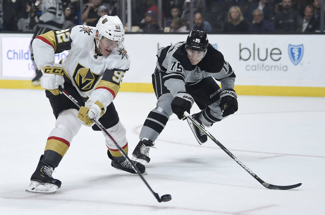 Vegas Golden Knights center Tomas Nosek, left, shoots the puck while pursued by Los Angeles Kin ...