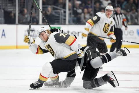 Los Angeles Kings right wing Adrian Kempe, back, falls onto Vegas Golden Knights center William ...