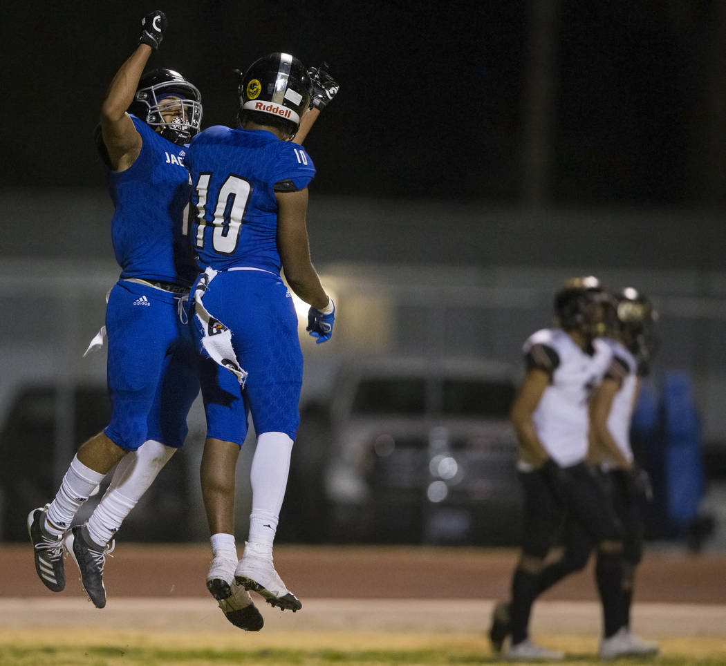 Desert Pines freshman wide receiver Deandre Moore (2) celebrates his touchdown catch with Deser ...