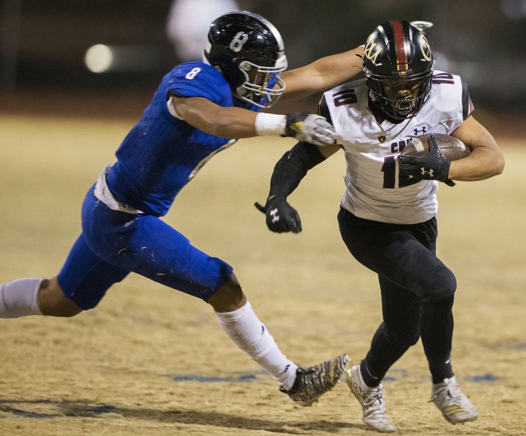 Faith Lutheran junior running back Amani El-Nawal (10) breaks the tackle of Desert Pines senior ...