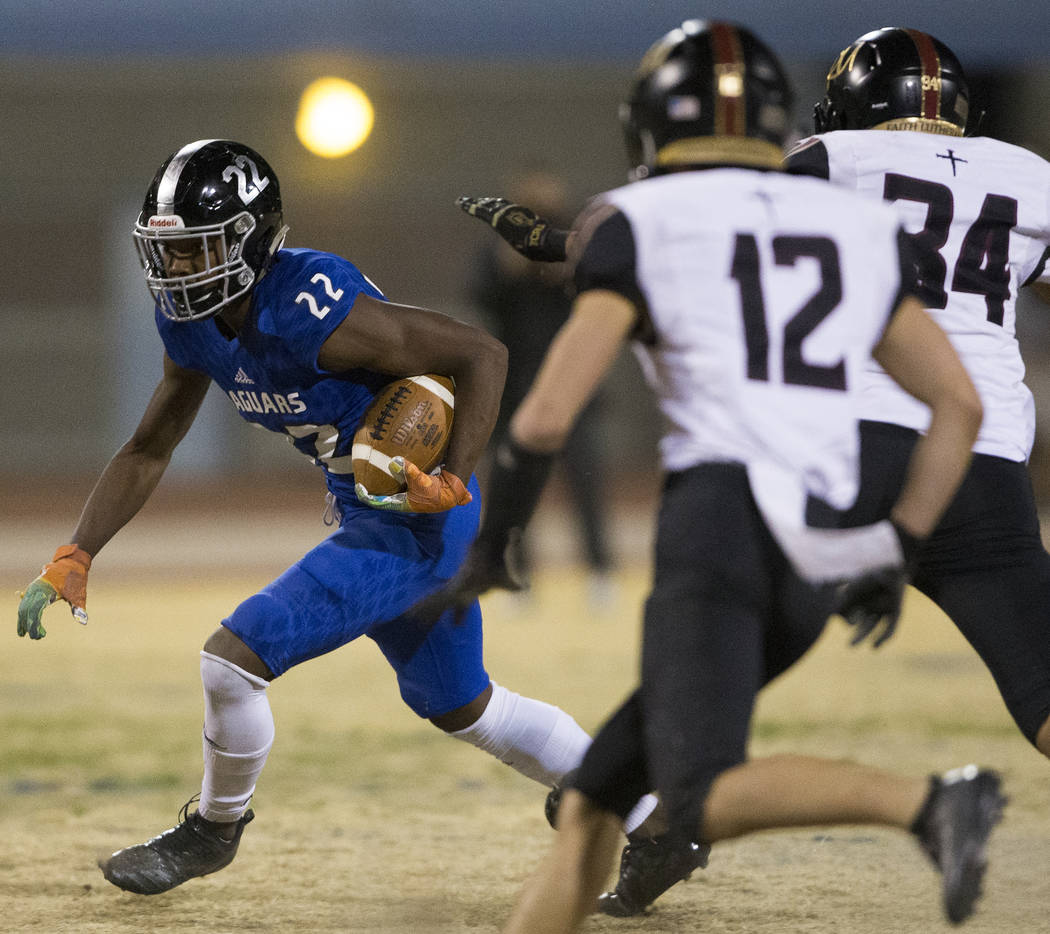Desert Pines sophomore running back Javontae Barnes (22) cuts up field past Faith Lutheran seni ...