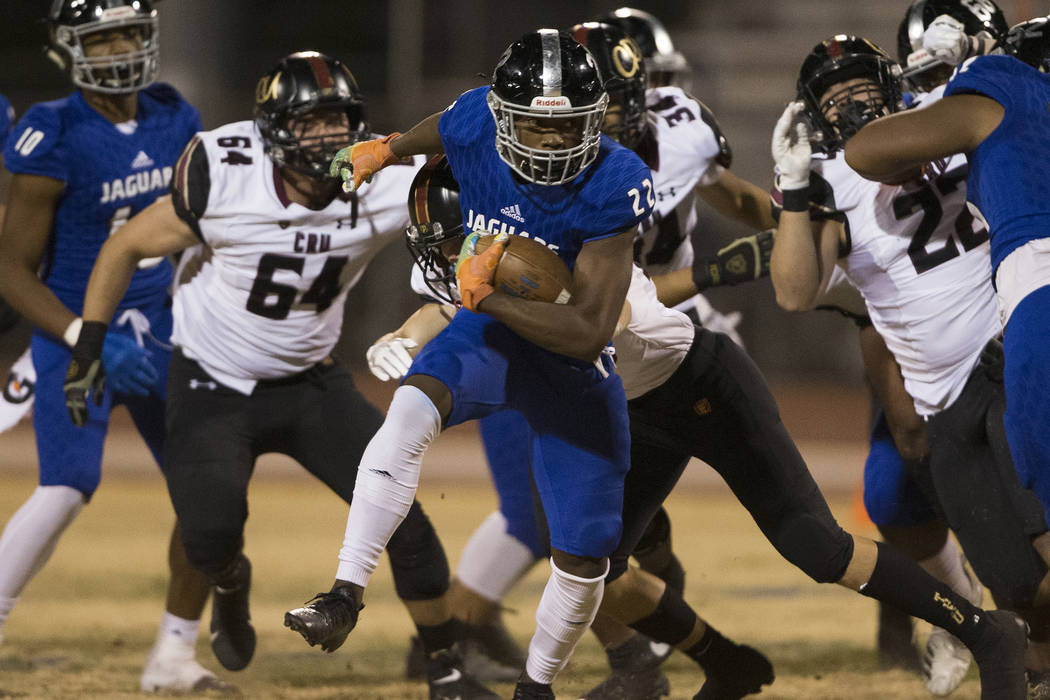 Desert Pines sophomore running back Javontae Barnes (22) breaks a big run past Faith Lutheran s ...