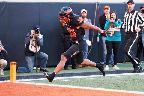 Oklahoma State running back Chuba Hubbard (30) leaps into the end zone with a touchdown in the ...
