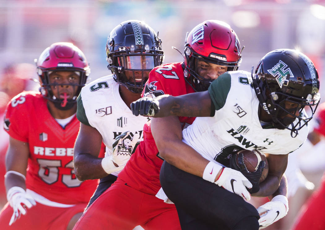 UNLV Rebels linebacker Austin Ajiake (27) tackles Hawaii Warriors wide receiver Cedric Byrd II ...