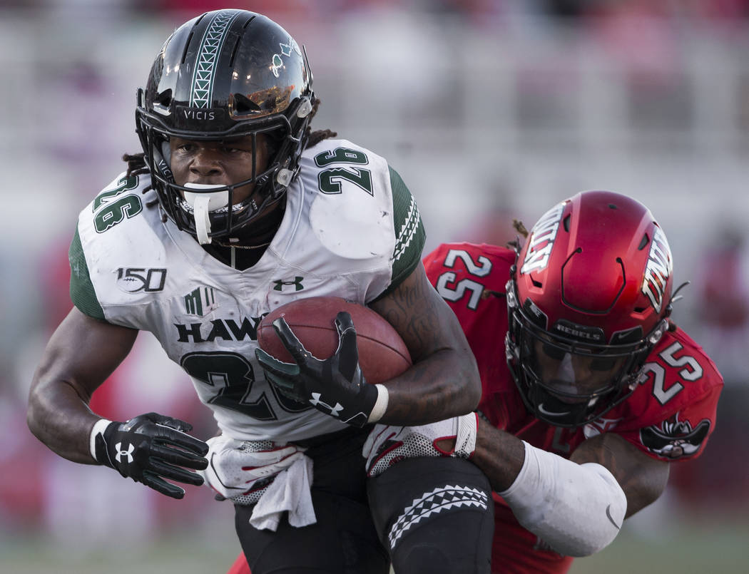 Hawaii Warriors running back Miles Reed (26) drives for the goal line with UNLV Rebels lineback ...