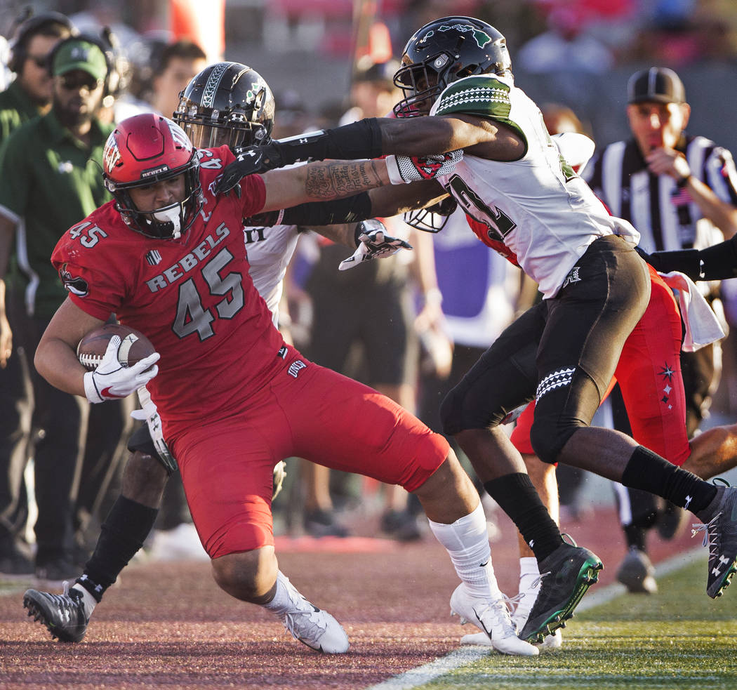 UNLV Rebels tight end Giovanni Fauolo Sr. (45) is knocked out of bounds by Hawaii Warriors defe ...