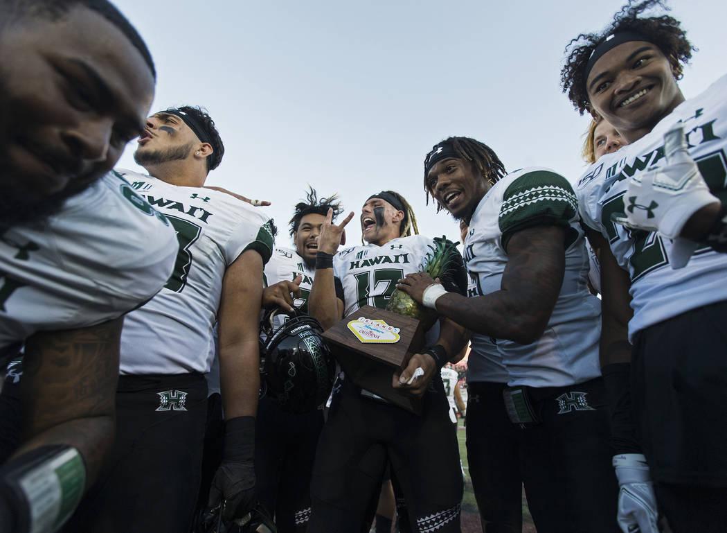Hawaii Warriors quarterback Cole McDonald (13) celebrates with teammates after beating UNLV 21- ...