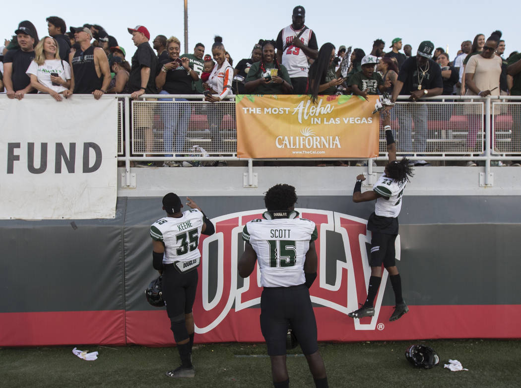 Hawaii Warriors defensive back Akil Francisco (23) celebrates with fans and teammates Paul Scot ...
