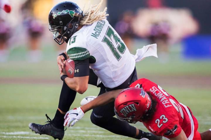 Hawaii Warriors quarterback Cole McDonald (13) is tackled by UNLV Rebels defensive back Greg Fr ...