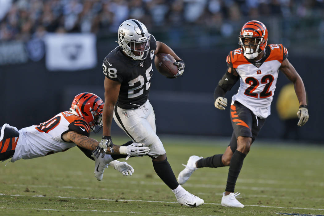 Oakland Raiders running back Josh Jacobs runs with the ball away from Cincinnati Bengals free s ...