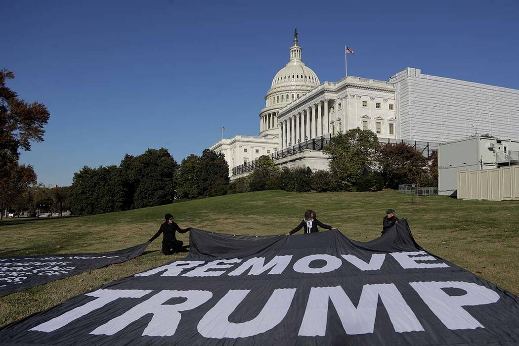 Demonstrators kneel near large banners on the lawn adjacent to the U.S. Capitol, while a top U. ...