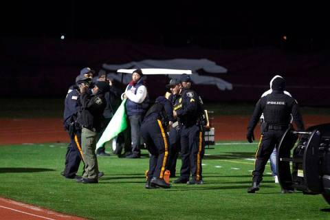 Police investigate the scene after a gunman shot into a crowd of people during a football game ...