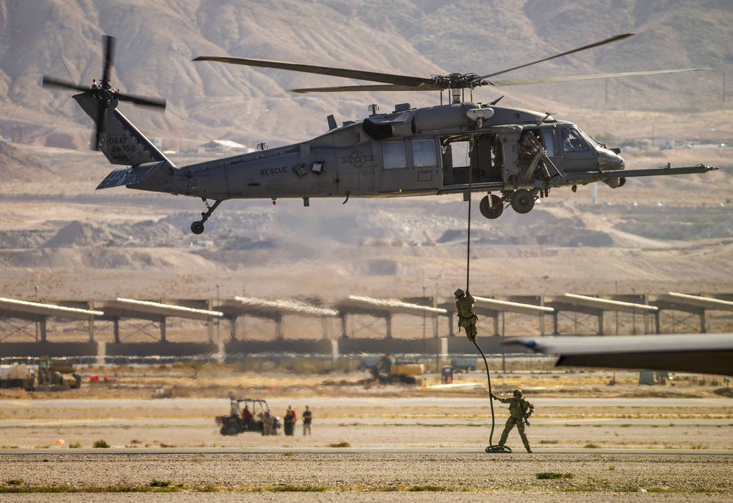 U.S. Air Force Pararescue members lower down onto the runway on a combined arms demo during the ...